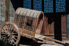 Ancient covered pull cart. An ancient, antique covered, pull cart parked in front of a preserved centuries old building Royalty Free Stock Images
