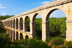 Ancient  aqueduct in summer forest. Tarragona Stock Images