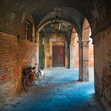 Ancient arcade & bikes in Lucca, Tuscany, square Royalty Free Stock Images