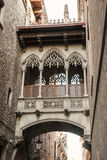 Ancient arch and balcony over Carrer del Bisbe. Gothic Quarter, Barcelona. Vertical photo Royalty Free Stock Images