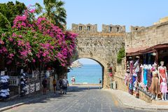 Ancient arch in old wall of Rhodes town with purple bougainvillea flowers in Rhodes town on Rhodes island, Greece. RHODES, GREECE - AUGUST 2017: Ancient arch in Stock Photos