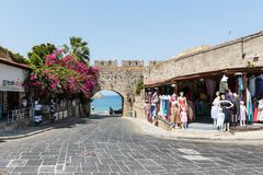 Ancient arch in old wall of Rhodes town with purple bougainvillea flowers in Rhodes town on Rhodes island, Greece. RHODES, GREECE - AUGUST 2017: Ancient arch in Stock Photography