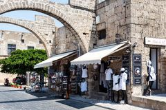 Ancient arch in old wall of Rhodes town with small shops under it in Rhodes town on Rhodes island, Greece. RHODES, GREECE - AUGUST 2017: Ancient arch in old wall Stock Photo