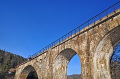 The ancient arch railway bridge from a stone. Against the sky Royalty Free Stock Images