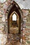 Ancient arches through the brick walls. With isolated window opening in neglected castle. Entrance and window opening on back wall Stock Photos