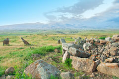 The ancient astrologica observatory Karahunj in Armenia. `Armenian Stonehenge`. View of the mountains and the blue sky. A pile of stones Stock Photo
