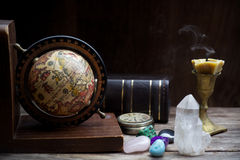 Ancient astrology. Old astrology globe and books with candle Stock Photography