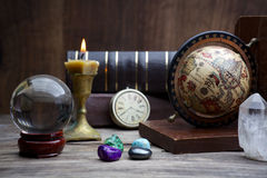 Ancient astrology. Old astrology globe and books with lighting candle Stock Photography