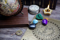 Ancient astrology. Old astrology globe and books with lighting candle Royalty Free Stock Photos
