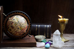Ancient astrology. Old astrology globe and books with lighting candle Stock Images
