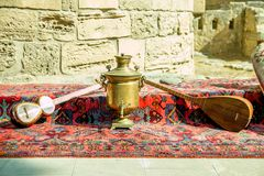 Ancient azerbaijani musical instruments tar and saz with old vintage azeri tea pot for boiling water. Ancient azerbaijani musical instruments tar and saz mock up Stock Image