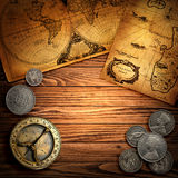 Ancient background. Old compass, coins and maps on wood background Royalty Free Stock Photos