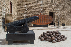 Ancient balck cannon with ammo in the arabian fort Royalty Free Stock Images