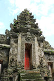 Ancient Balinese carved stone temple entrance with red door. Ancient Balinese temple with intricate carving and red door at Pura Kehen, Bali, Indonesia stock image