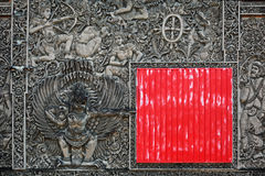 Ancient Balinese stone carving background with the red square shield Stock Photo