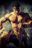 Ancient barbarian. Portrait of a handsome muscular ancient warrior with a sword Royalty Free Stock Photo
