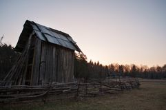 Ancient barn of wood, surrounded by a fence at dawn,. Rural landscape Stock Photos