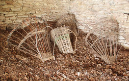 Ancient baskets  ( Alpine Gerla ) on the floor of a hut. Stock Photos