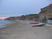 Ancient beach of Anzio to the sunset with some boats on the sand, Italy. Clear blue sky. Travel destination. Sea with waves. Beach of sand. Ancient ruins of a Royalty Free Stock Image