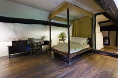 Ancient bedroom. With wooden bed, case and chair. Medieval cottage interior royalty free stock photo