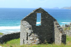 Ancient Beehive Ruins Dingle Penisula Ireland. Ruins of an ancient stacked stone hut on the Dingle Peninsula in Ireland. Overlooking the shockingly blue Atlantic Stock Images