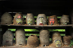 Ancient beehives with tribal masks Stock Images