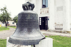 Ancient bell put on pedestal in front of the church of Cuza cast Stock Images