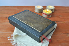 Ancient bible on a background of candles. Old book, the subject of Christianity religion bible, holy scripture on the background of candles Royalty Free Stock Images