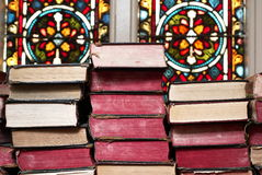 Ancient bibles stacked together. In church with stainglass windows royalty free stock photography