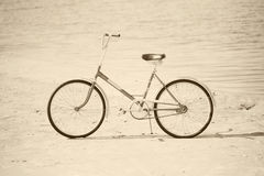 Ancient bicycle on beach - retro sepia Stock Images