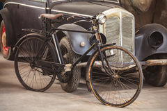 Ancient bike and car in an old shed. Ancient rusted bicycle and black car in an old shed Royalty Free Stock Photos
