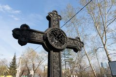 Ancient black iron forged cross banked among the sky in the Troitskoye cemetery 1842 of Krasnoyarsk city, in the spring. Black iron forged cross banked among the royalty free stock photography