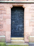 An ancient black studded door. An ancient black door studded with metal and with ornate hinges Royalty Free Stock Photos