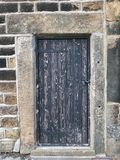 Ancient black wooden door with old faded peeling paint in a heavy stone frame with a closed bolt and metal hinges stock photography