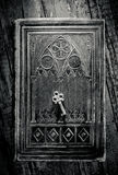 Ancient Book and Key. Old metal key lying on a decorated ancient book in black and white Stock Images