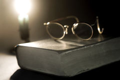 Ancient book lit by candle Royalty Free Stock Images