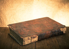 Ancient book on the old wooden table. Toned Royalty Free Stock Photos