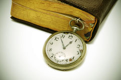 Ancient book and pocket watch royalty free stock photography