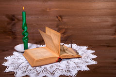 The ancient book, points and candle on a wooden table in the vil Stock Photo