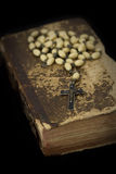 Ancient book with prayer beads. On black background royalty free stock photography
