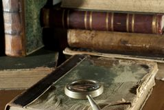 An antique book in a ragged cover and a magnifying glass on a blurred background of other old books royalty free stock image