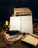 Ancient books on the old paper background. Ancient books with candle on the old paper background royalty free stock photography