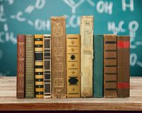 Ancient books in row on blackboard background. Ancient books paper art abstract brown dark Stock Images