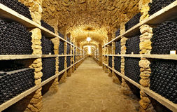 The ancient bottles of wine in the ancient cellar. The unique vi. Ntage wine in the cellar.Old bottles of wine in rows in wine cellar Royalty Free Stock Image