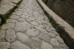 Ancient Boulder Street with Sidewalks, Herculaneum. Rocky Road, Kerb Stones and Sidewalk in Ancient Herculaneum. Herculaneum was buried in the eruption of Mount Royalty Free Stock Photography