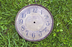Ancient brass clock face on grass Royalty Free Stock Photography