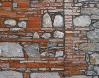 Ancient brick wall with large stone blocks inserted. stock photography