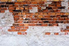 Ancient brick wall with plaster made of red-orange brick. Shattered surface. An abandoned house or an old factory. Stock Image