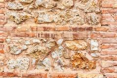 Ancient brick wall and stone wall. Red yellow,  grey texture. Stock Photos