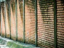 Ancient brick wall beside way after rain fall Royalty Free Stock Images